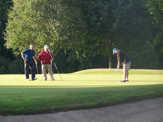Gerry Dwyer putting with Martin Lowry and Paul Galvin